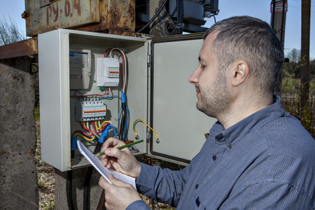 outdoor electricity: Outdoor electric substation, electrician engineer Writing Reading Of electricity Meter On Clipboard.