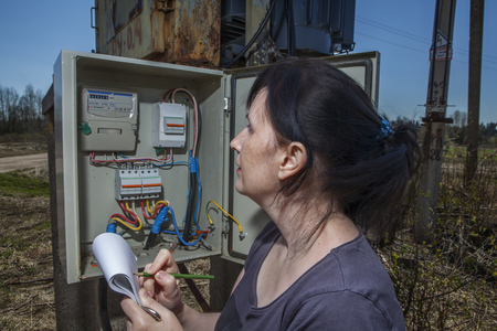 switchgear: Woman Technician reading the electricity meter to check consumption, standing near electricity switchgear  power transformer substation, outdoors. Stock Photo