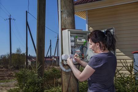 contador electrico: Mujer campesina en busca inswitchgear datos del medidor eléctrico montado en un poste de madera cerca de casa de campo en campo.