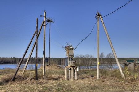 substation: Electricity distribution transformer, electrical power substation in the countryside spring sunny morning.