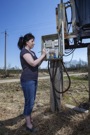 electric meter: Woman checking electric meter reading, standing near electricity switchgear  power transformer substation, outdoors. Stock Photo