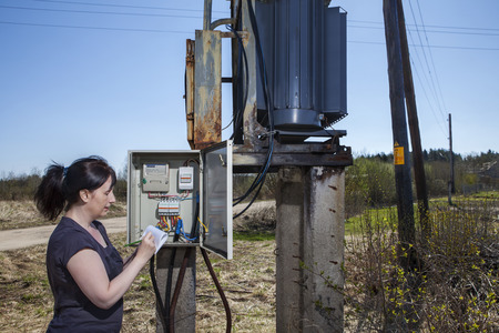 electricity meter: Electrician engineer  woman checking electricity meter and invoice,  standing near electricity switchgear  power transformer substation, outdoors.