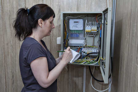 Woman takes readings of electricity meters, standing near the electrical switchgear inside.