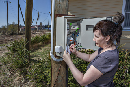 switchgear: Rural adult women to take readings of electricity meter outdoors.