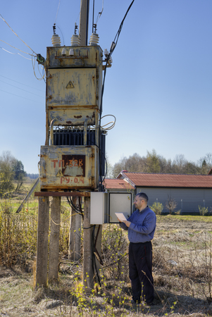 electricity substation: Outdoor rural electric substation, electrician engineer Technician reading the electricity counter to check consumption.