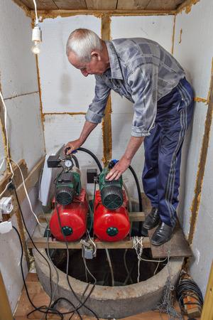 empleadas domesticas: sistema de suministro de agua de una casa de campo, granjero hace que el mantenimiento de la estación de bombeo en la habitación. Foto de archivo