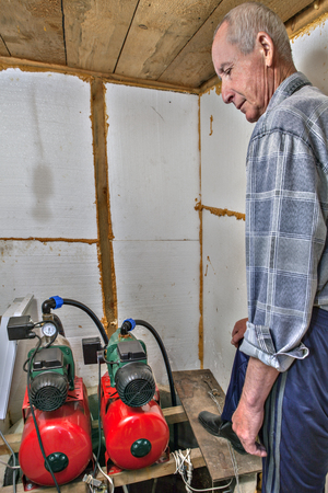 groundwater: Water supply system farmhouse, peasant makes adjustment of pumps in the pumping station room. Stock Photo