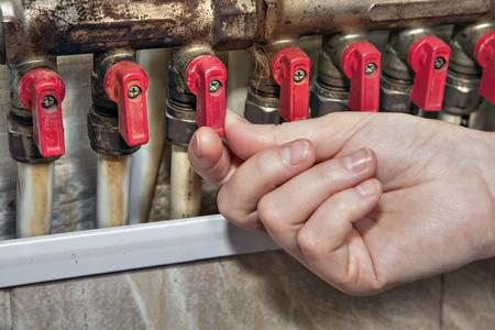 tuberias de agua: Inicio del sistema colector de distribuci�n de agua, v�lvulas de bloqueo el acceso a las tuber�as de agua, primer plano mano humana abre la v�lvula en la tuber�a.