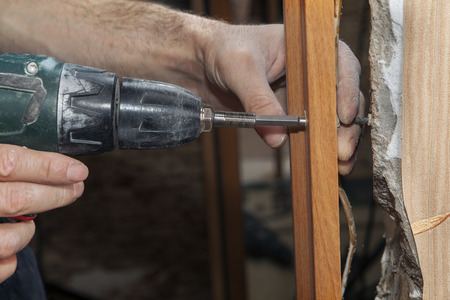 Woodworker screwed the jamb in doorway using a cordless drill electric screwdriver, close-up. Stock Photo