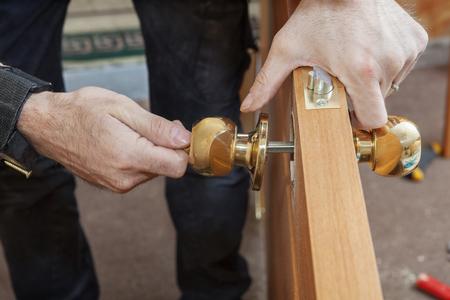 Carpenter Change deur, Het installeren van nieuwe deurknop met slot, close-up menselijke hend hold deurklink. Stockfoto