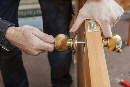 Carpenter Change door, Installing new door knob with lock, close-up human hend hold door handle. Stock fotó