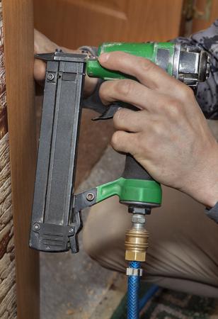 Door installation, close-up hand holding air tacker gun, fixing casing to the door frame. Standard-Bild