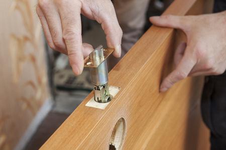 door knobs: Installation locked interior door knobs, close-up woodworker hands install lock.