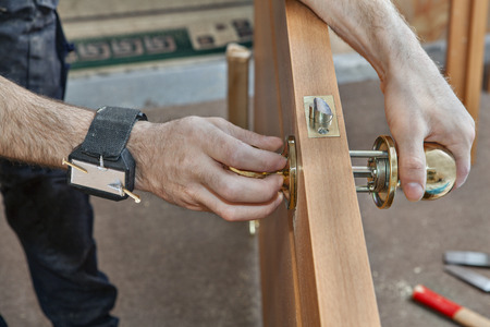 Installation of interior door, a carpenter installs handle with a lock in the door leaf using magnetic bracelet for holding screws, close-up.