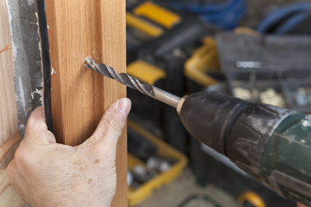 mounting holes: Installation of interior doors, close-up of electric drill drilling a hole in the wooden frame jamb.