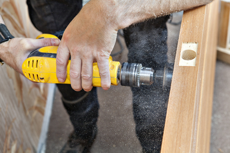mounting holes: Close-up of hands carpenter with yellow drill drilled big hole lock  through wooden interior door using hole saw drill bits, It is flying in the air and dust wood sawdust.