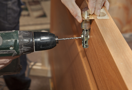deadbolt: Door installation, installing deadbolt lock using power drill, close-up.