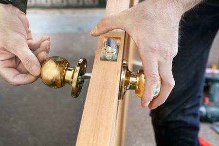 Door installation, worker Installs door knob, woodworker hands close-up.