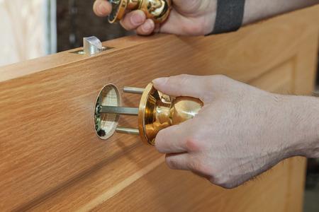 Installing new interior door,  close-up carpenter hand  holding spherical shaped brass door handle knob. Standard-Bild