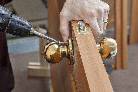 deadbolt: Install the door handle with a lock, Carpenter tighten the screw, using an electric drill screwdriver, close-up.