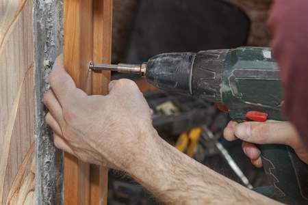 turnscrew: Carpenter fix jamb in doorway using a cordless drill electric screwdriver, close-up.