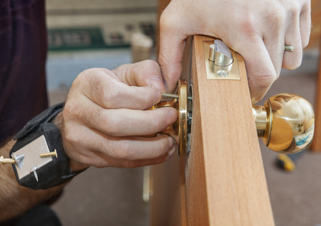 Install interior door, joiner mount knob with lock, hand with magnetic bracelet for holding screws close-up. Stock fotó