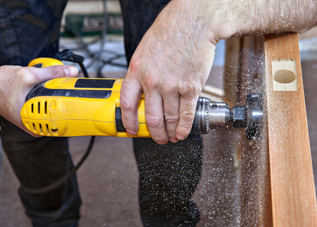 deadbolt: Install  interior wooden door doorknob lock using hole saw to begin cutting hole for deadbolt, close-up. Stock Photo