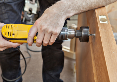 drill bit: Door installation, hands carpenter holding yellow  power drill with wood hole saw drill bit, drilling through the door to set the lock with a handle, close-up.
