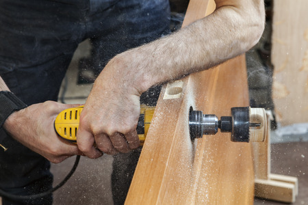deadbolt: Door installation, Install door lock, use hole saw to begin cutting hole for deadbolt, close-up carpenter hand holds yellow electric drill. Stock Photo