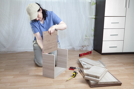 self assembly: Installation of wooden furniture made of particle board in the home, the woman assemble drawer.