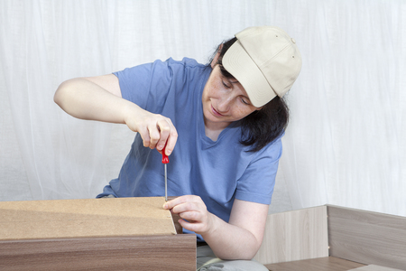 fastens: Furniture assemblage at home, woman fastens of sheet hardboard to bedside cabinet frame , tightening screw with a hand screwdriver. Stock Photo