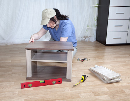 self assembly: One caucasian woman putting together self assembly furniture while sitting on floor. Stock Photo