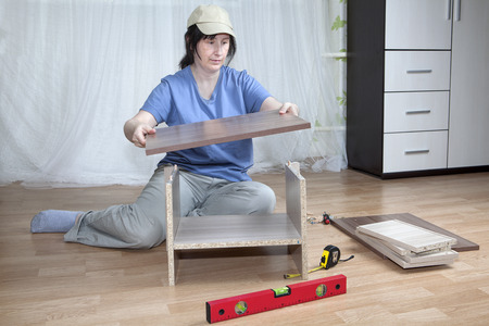 self assembly: Self �assembly of furniture, a housewife assembles nightstand in the interior of the apartment, sitting on the floor.