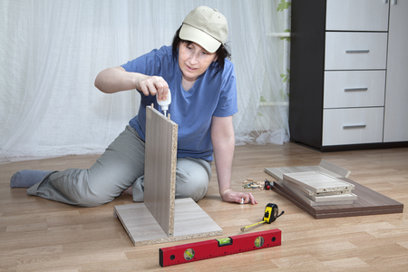 assemble: Woman putting together self assembly furniture assemble flat pack. Stock Photo