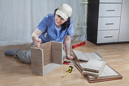 smearing: Furniture assembling at home, Woman putting together board drawers, smearing glue chipboard ends.