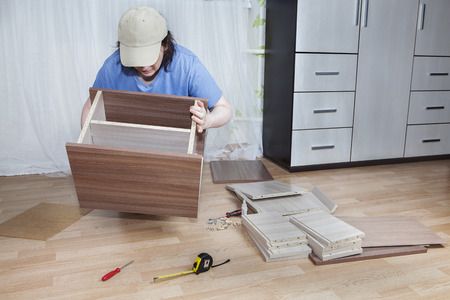 assemble: Assemble furniture, woman carpenter apply glue and clamp the two boards together.