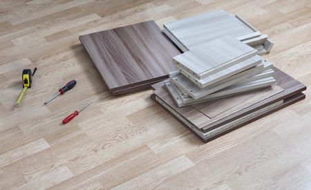muebles paquete plano acostado en el piso en su casa junto a las herramientas manuales para el montaje. Foto de archivo