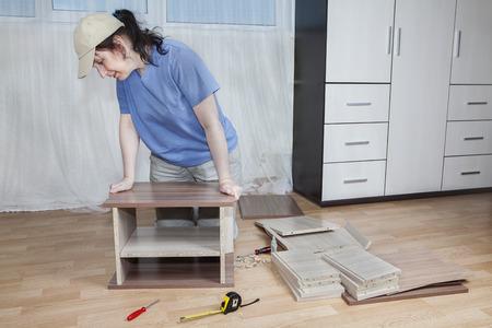 bedside tables: Flat pack furniture, woman assembling wooden bedside tables, using glue, on floor in living room.
