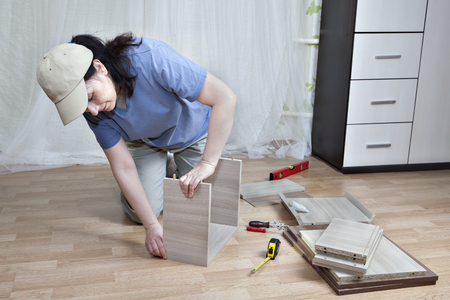 self assembly: Assembling drawer bedside table, the woman mounts the boards together.