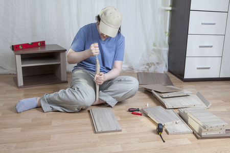 assemble: Assemble wooden furniture, woman putting together self assembly furniture.