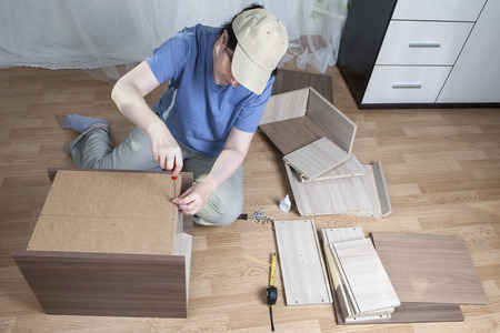fastens: Assembling of furniture at home, woman fastens a sheet of hardboard in the back of the nightstand, using a hand screwdriver. Stock Photo