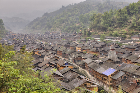 xing: Zhaoxing Dong Village, Guizhou Province, China -  April 7, 2010:  Tile roofs of wooden houses in the mountain village of Dong ethnic minority, misty morning, spring.