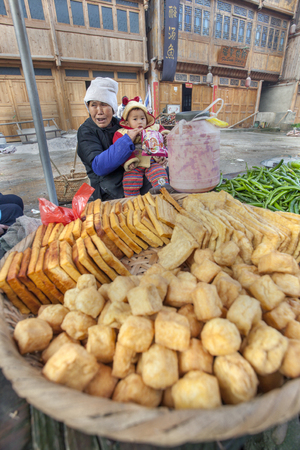 tradeswoman: Zhaoxing Dong Village, Guizhou Province, China -  April 8, 2010: Street trade in the Asian countryside, an elderly woman holding a child, sells fried tofu. Editorial