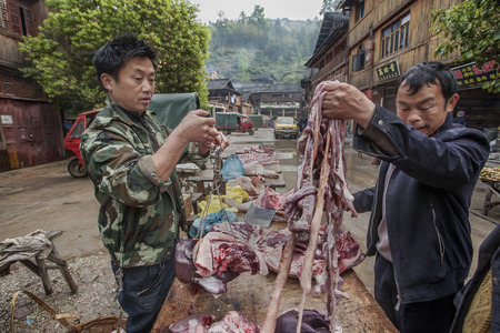 entrails: Zhaoxing Dong Village, Guizhou Province, China -  April 8, 2010: Asiatic buying pig entrails from a street vendor in the Chinese countryside.