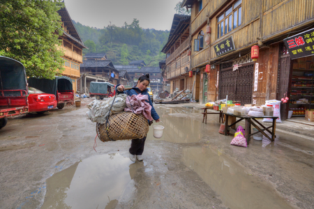 tradeswoman: Zhaoxing Dong Village, Guizhou, China -  April 8, 2010: Street tradeswoman with a yoke on his shoulder, carries a large wicker cage on street settlements of ethnic minorities passed wooden houses. Editorial