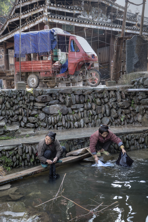 dong: Zhaoxing Dong Village, Guizhou Province, China -  April 8, 2010: Two Chinese women rinse laundry in water countryside river, near the cobblestone the seafront and parked motor tricycle. Editorial