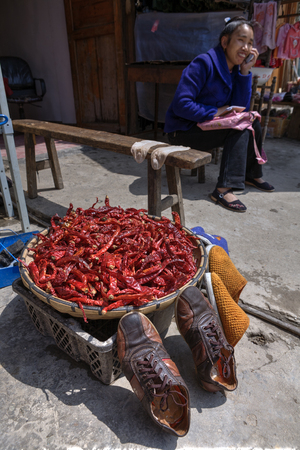 tradeswoman: Zhaoxing Dong Village, Guizhou Province, China -  April 8, 2010: Outdoor trade on rural street, dried chili is in a large basin, next drying shoes and socks. Editorial