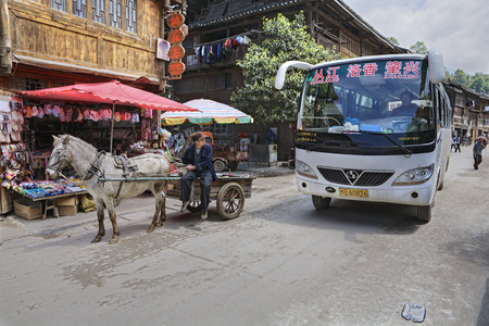 horse drawn: Zhaoxing Dong Village, Guizhou Province, China -  April 8, 2010: Chinese Public transport in the countryside of ethnic minorities,  shuttlebus and horse drawn vehicle. Editorial