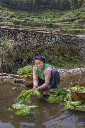 en cuclillas: Zhaoxing Dong Village, Guizhou Province, China -  April 8, 2010: Asian woman washing salad leaves in water rural river, squatting and smiling.