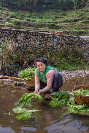 cuclillas: Zhaoxing Dong Village, provincia de Guizhou, China - 8 abril 2010: ensalada de lava de la mujer asi�tica deja en agua rural r�o, en cuclillas y sonriente.